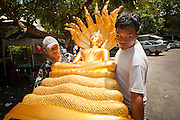 "05 JULY 2011 - BANGKOK, THAILAND:    Men unload Buddha statues from a truck at a store on Bamrung Muang Street in Bangkok. Thanon Bamrung Muang (Thanon is Thai for Road or Street) is Bangkok's ""Street of Many Buddhas."" Like many ancient cities, Bangkok was once a city of artisan's neighborhoods and Bamrung Muang Road, near Bangkok's present day city hall, was once the street where all the country's Buddha statues were made. Now they made in factories on the edge of Bangkok, but Bamrung Muang Road is still where the statues are sold. Once an elephant trail, it was one of the first streets paved in Bangkok, it is the largest center of Buddhist supplies in Thailand. Not just statues but also monk's robes, candles, alms bowls, and pre-configured alms baskets are for sale along both sides of the street.      PHOTO BY JACK KURTZ"