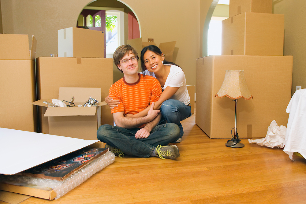A portrait of a mixed race couple embracing on the floor of their new house surrounded by moving boxes.  Man is early 30's Caucasian and woman is late 20's Japanese American.20050910_MR_A.20050910_MR_B.20050910_PR_A