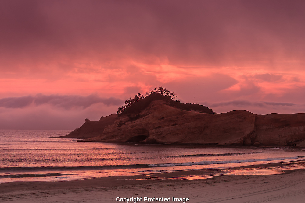 As evening fog moves toward the Oregon coast a fiery sunset erupts over Cape Kiwanda