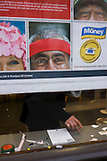 The hands and fingers of an anonymous customer seen through a city Post Office window, behind a pension savings ad.
