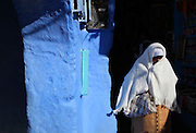 A woman shrouded in a headscarf and shawl against a blue wall of the medina or old town of Chefchaouen in the Rif mountains of North West Morocco. Chefchaouen was founded in 1471 by Moulay Ali Ben Moussa Ben Rashid El Alami to house the muslims expelled from Andalusia. It is famous for its blue painted houses, originated by the Jewish community, and is listed by UNESCO under the Intangible Cultural Heritage of Humanity. Picture by Manuel Cohen
