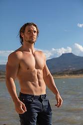 good looking shirtless muscular man by a lake