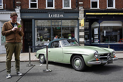 © Licensed to London News Pictures. 17/06/2018. LONDON, UK. A man stands next to a 1959 Mercedes-Benz 190SL at the 6th Annual Classic and Supercar Pageant held at St John's Wood High Street.  Traditionally taking place on Fathers' Day, the show brings together an eclectic mix of exotic and popular vehicles attracting visitors young and old and raises funds for the local charity, The St John's Hospice.  Photo credit: Stephen Chung/LNP