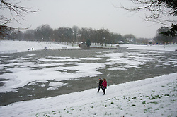 LIVERPOOL, ENGLAND - Friday, January 18, 2013: Sefton Park's Boating Lake is frozen over as a couple walk past during the first snow fall of the winter in South Liverpool's Victorian Park. (Pic by David Rawcliffe/Propaganda)