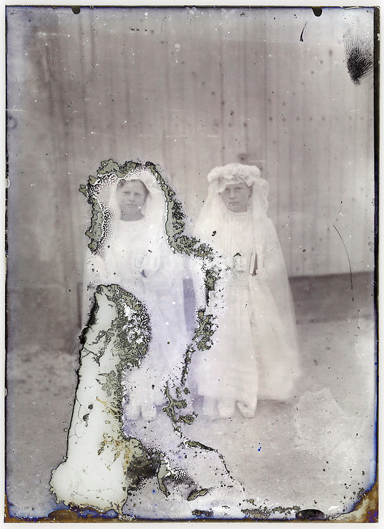 severely eroding glass plate with two young girls in holy communion clothing