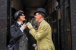 © Licensed to London News Pictures. 14/07/2019. LONDON, UK.  London, UK. 14 July 2019.   An elegantly dressed couple take part in The Grand Flâneur walk.  Starting at the Beau Brummell statue on Jermyn Street, the walk coincides with the 20th anniversary of The Chap magazine and is defined as a walk without purpose, celebrating the art of the flâneur, oblivious to going anywhere specific, and an antidote to the demands of modern life and the digital smartphone.  Similar walks are taking place in Dusseldorf and Los Angeles.  Photo credit: Stephen Chung/LNP