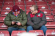 A Pair Scunthorpe united fans in look at the match program prior to the EFL Sky Bet League 1 match between Scunthorpe United and Rotherham United at Glanford Park, Scunthorpe, England on 10 February 2018. Picture by Craig Zadoroznyj.
