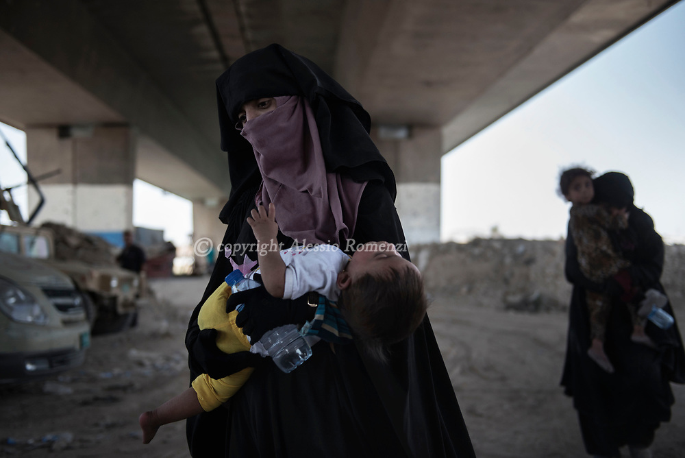 IRAQ, Mosul: After they managed to escape, civilian women walk back from the fighting area in the old city of Mosul. Alessio Romenzi