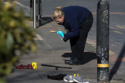 © Licensed to London News Pictures . 25/03/2018 . Manchester , UK . Forensic scenes of crime examiners work as police close off a section of Upper Chorlton Road in Chorlton-cum-Hardy after a man armed with a sword was detained . Clothes , used Tasers and a police baton lie scattered on the road and pavement following a reported struggle with a man , who was tasered at the scene . Photo credit : Joel Goodman/LNP