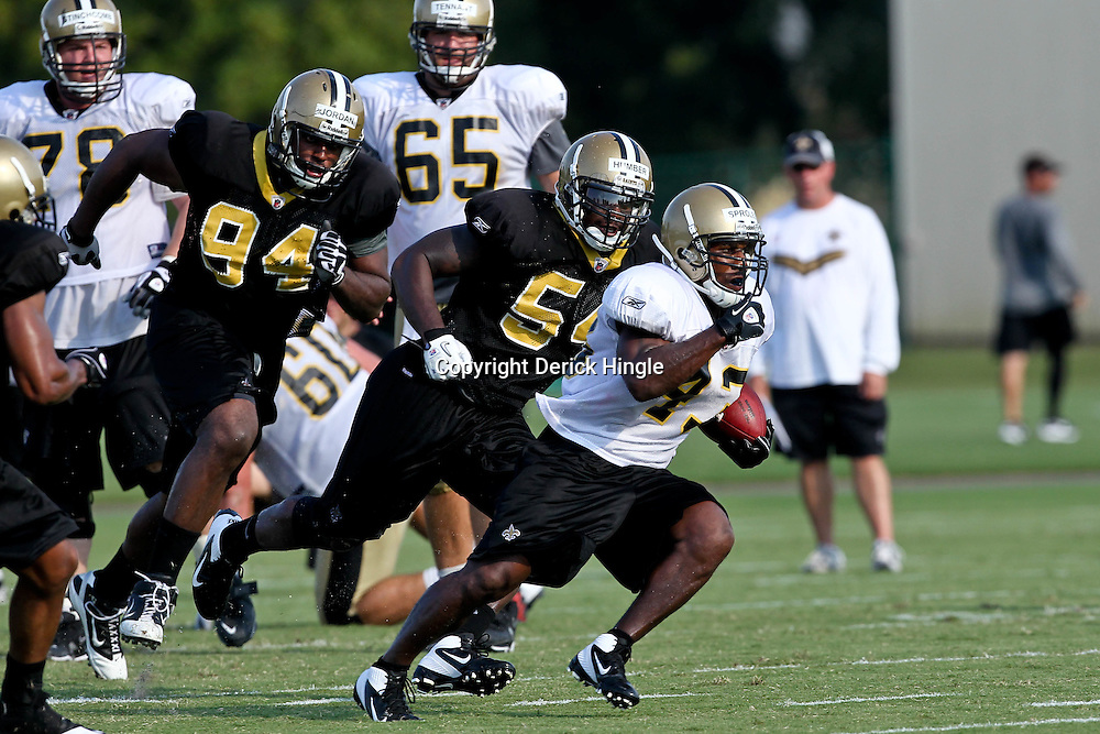 August 6, 2011; Metairie, LA, USA; New Orleans Saints running back Darren Sproles (43) sprints away from linebacker Ramon Humber (54) and defensive end Cameron Jordan (94) during training camp practice at the New Orleans Saints practice facility. Mandatory Credit: Derick E. Hingle