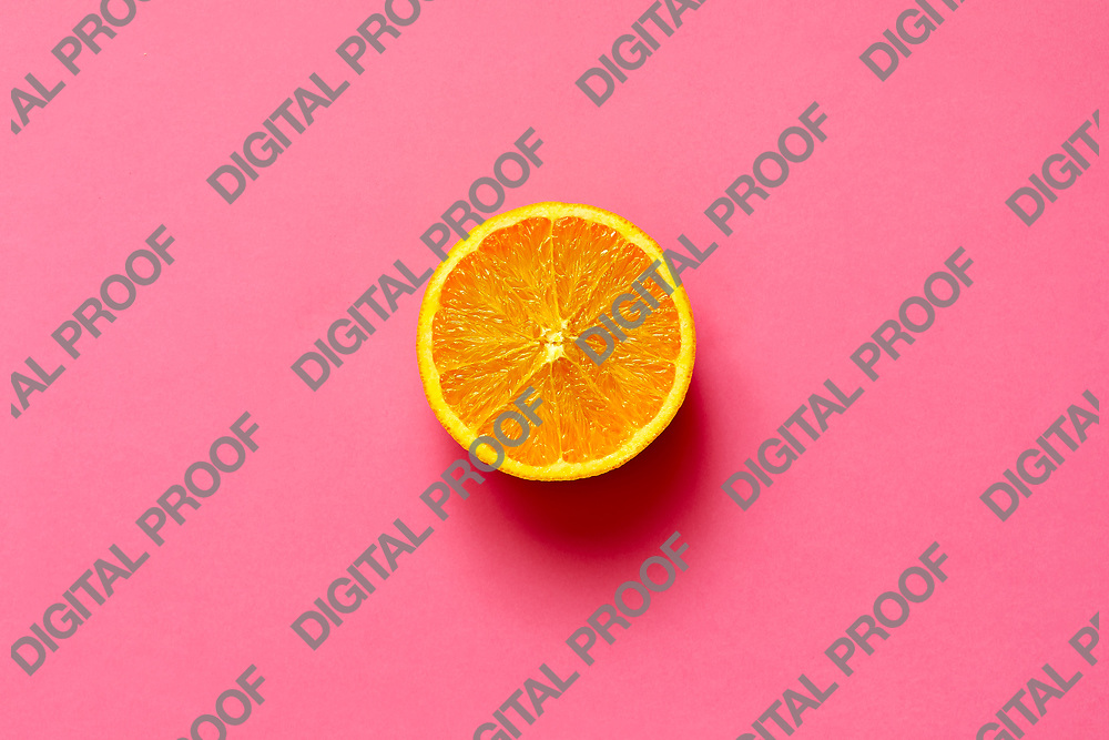 Orange fruit. Orange half fruit sliced isolate on fuscia background seen from above flatlay style, close up.
