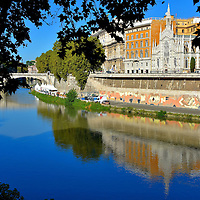 Tiber River from Pointe Cavour in Rome, Italy<br /> The Tiber River flows for over 250 miles but the most beautiful section can be enjoyed an hour or so after sunrise when golden light bathes the western bank. Start your morning near the bridge called Pointe Cavour. Then walk south along the tree-lined path on the eastern side in order to fully appreciate the spectacular scenery.  Take time to greet the locals who are out walking their dogs.  This makes a perfect 45 minute stroll towards Vatican City.  Your first sight is the Catholic church called Chiesa del Sacro Cuore del Suffragio.
