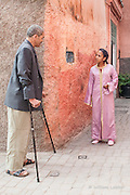 Man and girl have a conversation in the narrow street of the old medina in Marrakesh of Morocco.