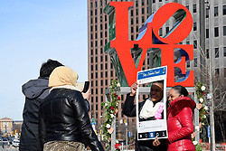 People are seen taking pictures for Instagram in front of a with bouquets of roses decorated LOVE Park statue, in Philadelphia, PA, on Valentines Day, February 14, 2019.