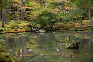 A small wooden boat and autumn reflections in the pond at the Saiho-ji Garden (Temple of Moss) Kyoto,  Japan