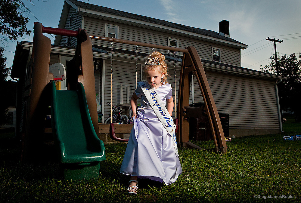 The latest winner of the Little Miss Chauncey Dover Spring Festival, Tomi Sue Schweikert, 5, poses for a portrait outside her McArthur, Ohio, home, on Friday evening, June, 12, 2009.