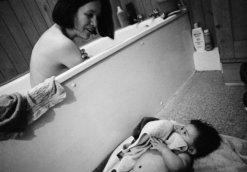 """Eye Contact."" A mother peers over the bath to keep watch over her five month-old baby daughter who is lying on a matt, holding a towel to her face. The infant has had her own time in the water and the mum has taken the opportunity to bathe too. They both look into each other's eyes in a picture of love, trust and joy. This is from a documentary series of pictures about the first year of the photographer's first child Ella. Accompanied by personal reflections and references from various nursery rhymes, this work describes his wife Lynda's journey from expectant to actual motherhood and for Ella - from new-born to one year-old."