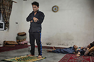 22/05/15. Awbar Village, Darbandikhan area, Iraq. -- Laith prays in the evening while his son rests together with his uncle Saif.