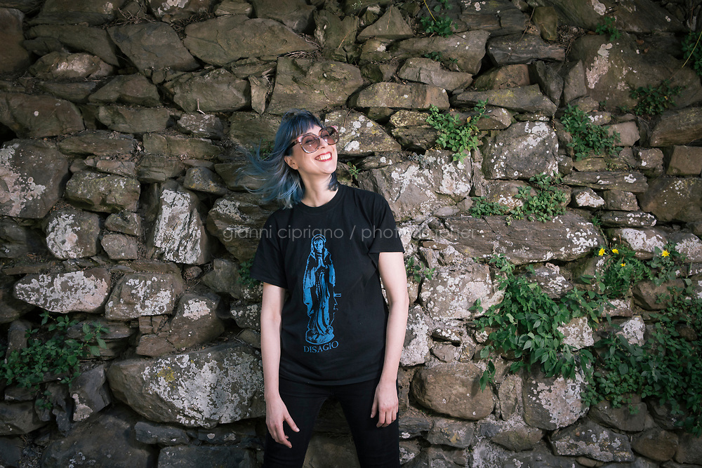 MANAROLA, ITALY - 1 JUNE 2017: Margherita Ermirio, 32, a local who has spent years abroad and is now the pillar of the battle to restore dry stone walls and preserve the terracing, poses for a portrait in Manarola, Italy, on June 1st 2017.<br /> <br /> Given its jagged coastline and manifold mountainous chains, Italy is believed to hold a record in Europe with an estimated 300,000 hectares of terracing, and 170,000 kilometers of dry stone walls&mdash; 20 times the length of the Great Wall of China.<br /> Liguria, the narrow half-moon shaped region along the northern<br /> Thyrrenian sea, has the highest concentration, and terracing is in<br /> poor shape there. In Vernazza, almost half of the terracing is in<br /> ruins.<br /> <br /> Terraced vineyards, apple and lemon groves horizontally run around the green slopes of the Cinque Terre. The stone walls have allowed such vital cultivation in the area and prevented land slides. Since the 1960s, the ancient walls have been largely<br /> abandoned, posing hydro-geological threats to the same villages during<br /> heavy rains and, in general, as time passes.<br /> <br /> Since the 2012 flood - when tons of mud invaded the<br /> village&rsquo;s main road, shops and and homes, isolating the area and<br /> taking three lives - Margherita Ermirio has agreed with the various land lords to take<br /> over 6,000 square meters of land parcels that needed to be cleaned up,<br /> in order to fix them and thus prevent land slides, but also to show to<br /> the younger generations that agriculture is still possible in the<br /> Cinque Terre.
