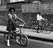 Two girls on bicycles in the street Lenton Nottingham UK 1989