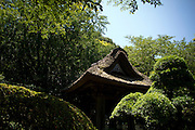 KAMAKURA, JAPAN -   H?koku-ji - Traditional thatch roof in the middle of the green.  July 2011
