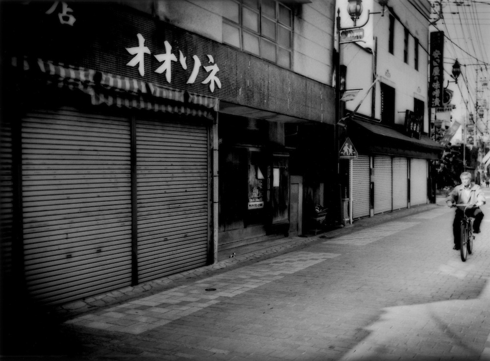 """Shutters drawn down on Chichibu City's """"shoutengai"""" shopping street of closed down shops during the business week, reflect lean times, Saitama Prefecture, Japan.  Japanese have coined the phrase, """"shuttered street"""" to describe this steady decline of businesses on local """"shoutengai"""" shopping streets."""