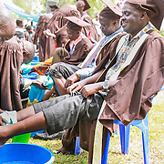 CAPTION: Edward Okiror of World Renew Uganda is seen here having his feet washed by a fellow graduand. The graduands' act of washing each other's feet is similar to what Christ did for the Disciples on Passover night, in order to demonstrate how a true leader will humble himself for those who follow him or her. In the same way, the graduands were encouraged to be both servants and leaders. LOCATION: Kaberamaido, Kaberamaido District, Uganda. INDIVIDUAL(S) PHOTOGRAPHED: Edward Okiror (right) and TLT graduands.