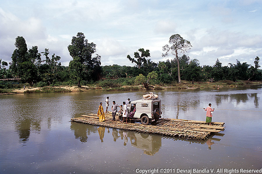 Simple eco-friendly technology at work.People and a Jeep are transported from one .river bank to the other on a bamboo raft moved by two men pulling at the iron cable suspended between the two river banks,Wayanad,Kerala.