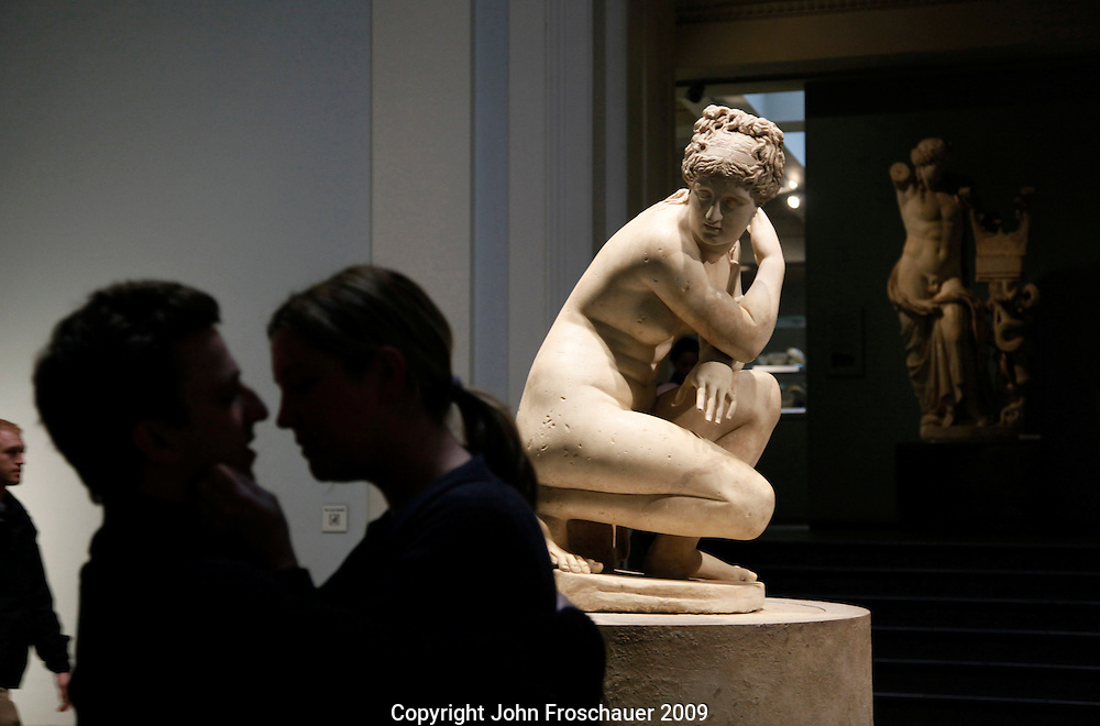 """A couple kisses with a 1st or 2nd century AD Roman copy of a Greek Venus watching in the British Museum in London England on Saturday, Nov. 14, 2009. The description of the naked Aphridite says """"Here the goddess Venus is surprised as she bathes . . ."""" possibly by the young couple. (Photo/John Froschauer)EDITORIAL USE ONLY"""