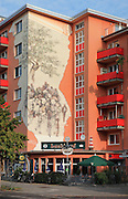 Apartment building with a restaurant on the ground floor and a mural painted on the wall, Kreuzberg, Berlin, Germany. Picture by Manuel Cohen
