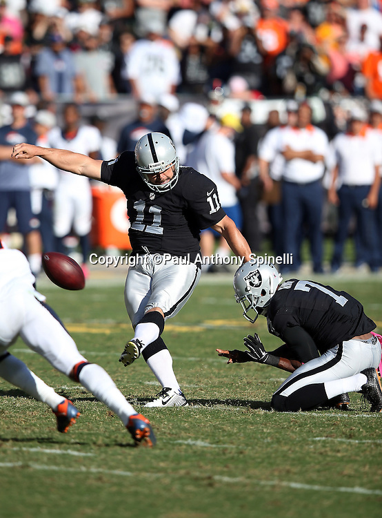 Oakland Raiders punter Marquette King (7) holds as Oakland Raiders kicker Sebastian Janikowski (11) kicks a fourth quarter field goal that cuts the Denver Broncos lead to 16-10 during the 2015 NFL week 5 regular season football game against the Denver Broncos on Sunday, Oct. 11, 2015 in Oakland, Calif. The Broncos won the game 16-10. (©Paul Anthony Spinelli)