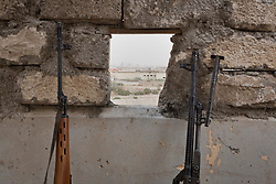 © Licensed to London News Pictures. 28/09/2014. Rabia, Iraq. A view of ground held by Islamic State insurgents is seen from a Syrian-Kurdish position in the Iraqi border town of Rabia.<br /> <br /> Facing each other across the Iraq-Syria border, the towns of Al-Yarubiyah, Syria, and Rabia, Iraq, were taken by Islamic State insurgents in August 2014. Since then The town of Al-Yarubiyah and parts of Rabia have been re-taken by fighters from the Syrian Kurdish YPG. At present the situation in the towns is static, but with large exchanges of sniper and heavy machine gun fire as well as mortars and rocket propelled grenades, recently occasional close quarter fighting has taken place as either side tests the defences of the other. Photo credit: Matt Cetti-Roberts/LNP