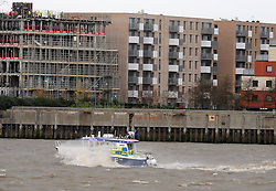 &copy; Licensed to London News Pictures. 05/12/2013<br /> A police boat battles the winds on the Thames as it heads into London at the Thames Barrier.<br /> The Met office has given a severe weather warning for parts of the UK and The Thames Barrier will close at 10pm tonight(05/12/2013) to protect London from a combined high tide and tidal surge in the Thames estuary.<br /> Photo credit :Grant Falvey/LNP