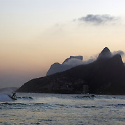 A surfer catches a wave at Ipanema Beach with the twin peaks of Dois imaos in the distance. Rio de Janeiro, Brazil. 8th August 2010. Photo Tim Clayton...