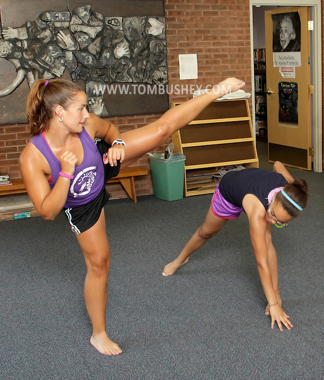 Belinda Ligotino, right,  of Camp Shawangunk ducks under a kick by Colleen Zimmerman, also from the camp, during a Capoeira class taught by Gustavo Caldas of the Vanaver Caravan at the Ellenville Public Library on Tuesday, July 17, 2012. Camp Shawangunk sponsors the class, which meets on Tuesdays at 2 p.m., but the class is open to anyone 12 and older. The class ends on Aug. 7. Capoeira is an Afro-Brazilian martial art form that integrates music and dance.