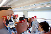 Florence, Italy - 28 April, 2012: First class passengers read newspapers on the Milano bound ITALO, Europe's first private operator of high-speed, domestic trains in Italy, in Florence, Italy, on April 28, 2012. The company's president is Ferrari chairman Luca Cordero di Montezemolo, one of the shareholders along with other private entrepreneurs like luxury businessmen Diego Della Valle, the French railway company, Italy's largest retail bank and the country's largest insurer. Italy's NTV (Nuovo Trasporto Viaggiatori) is the first company in Europe to compete with the state-run Trenitalia on high-speed service. When at full regime at the end of the year, 25 innovative trains will connect nine Italian cities, from Salerno to Milan, from Turin to Venice at 300km per hour. Italo passengers will board on stable trains that do not rely on a locomotive car, but has engines underneath each of the 11 carriages to increase capacity as well as safety.<br /> <br /> Ph. Gianni Cipriano for The New York Times