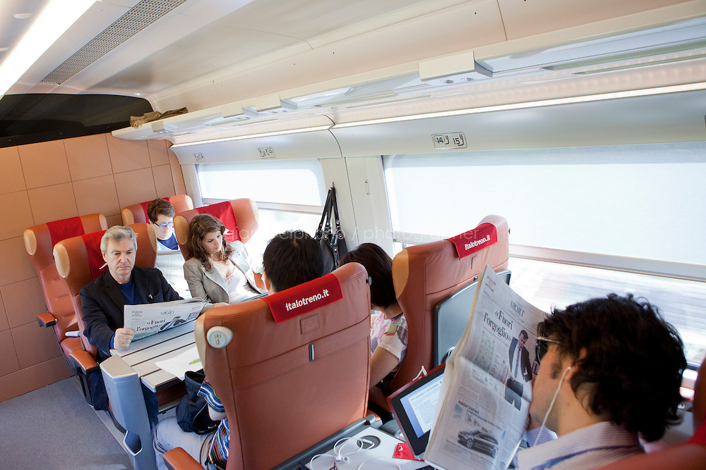 Florence, Italy - 28 April, 2012: First class passengers read newspapers on the Milano bound ITALO, Europe&rsquo;s first private operator of high-speed, domestic trains in Italy, in Florence, Italy, on April 28, 2012. The company&rsquo;s president is Ferrari chairman Luca Cordero di Montezemolo, one of the shareholders along with other private entrepreneurs like luxury businessmen Diego Della Valle, the French railway company, Italy&rsquo;s largest retail bank and the country&rsquo;s largest insurer. Italy&rsquo;s NTV (Nuovo Trasporto Viaggiatori) is the first company in Europe to compete with the state-run Trenitalia on high-speed service. When at full regime at the end of the year, 25 innovative trains will connect nine Italian cities, from Salerno to Milan, from Turin to Venice at 300km per hour. Italo passengers will board on stable trains that do not rely on a locomotive car, but has engines underneath each of the 11 carriages to increase capacity as well as safety.<br /> <br /> Ph. Gianni Cipriano for The New York Times