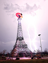 Lightning rips through the night sky Thursday, April 3, 2014 behind a replica Eiffel Tower in Paris, Texas as a severe thunderstorm moved through the Southern part of Lamar County bringing high winds, rain and hail.  (AP Photo, The Paris News News)