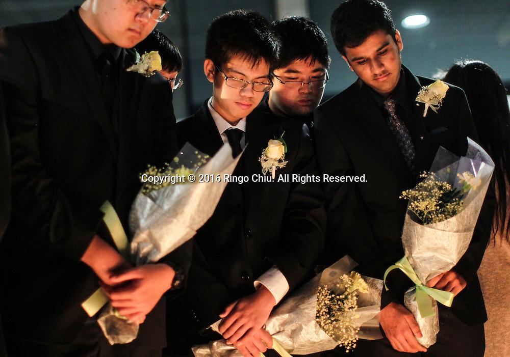 1月25日,美国洛杉矶县阿卡迪亚市,同学手拿鲜花参加在阿卡迪亚高中举办的烛光晚会悼念两名在家中被害身亡华裔兄弟。上星期五,美国华裔聚居的洛杉矶县阿卡迪亚市发生双尸凶杀案,2名华裔高中学生为15岁的林安东尼(Anthony Lin)和他的哥哥,16岁的林威廉(William Lin),怀疑被姑父在家中用钝器杀害,其后,杀害两兄弟的姑父搭乘国泰航空离开美国,但香港国际机场被当地警察逮捕。新华社发 (赵汉荣摄)<br /> Students hold a candlelight at Arcadia High School Monday night, January 25, 2016, during a candlelight vigil for the two brothers killed by their uncle in Friday, in Arcadia, California, the United States. Two brothers, 15 and 16, were found by their parents Friday at their home near school. They appeared to have suffered blunt force trauma and were pronounced dead at he scene, official said. They were identified as Arcadia High School students William and Anthony Lin, according to a statement from the Arcadia Unified School District. Their 44-year-old uncle, identified as Deyun Shi, who is suspected of killing the boys after becoming enraged that his wife had obtained a restraining order against him and begun divorce proceedings, fled on a plane to China, but was taken into custody by Hong Kong authorities Saturday as his plane arrived at Hong Kong International Airport, officials said. Authorities are working to have him returned to California. (Xinhua/Zhao Hanrong)(Photo by Ringo Chiu/PHOTOFORMULA.com)<br /> <br /> Usage Notes: This content is intended for editorial use only. For other uses, additional clearances may be required.