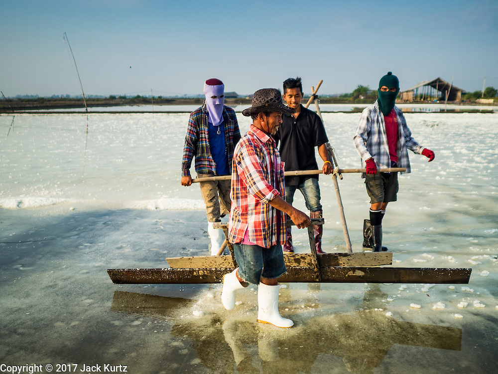 22 FEBRUARY 2017 - BAN LAEM, PETCHABURI, THAILAND: Workers carry a salt rake through a field during the salt harvest in Petchaburi province of Thailand, about two hours south of Bangkok on the Gulf of Siam. Salt is collected in coastal flats that are flooded with sea water. The water evaporates and leaves the salt in large pans. Coastal provinces south of Bangkok used to be dotted with salt farms, but industrial development has pushed the salt farms down to remote parts of Petchaburi province. The harvest normally starts in early February and lasts until early May, but this year's harvest was delayed by a couple of weeks because of unseasonable rain in January that flooded many of the salt collection ponds.    PHOTO BY JACK KURTZ