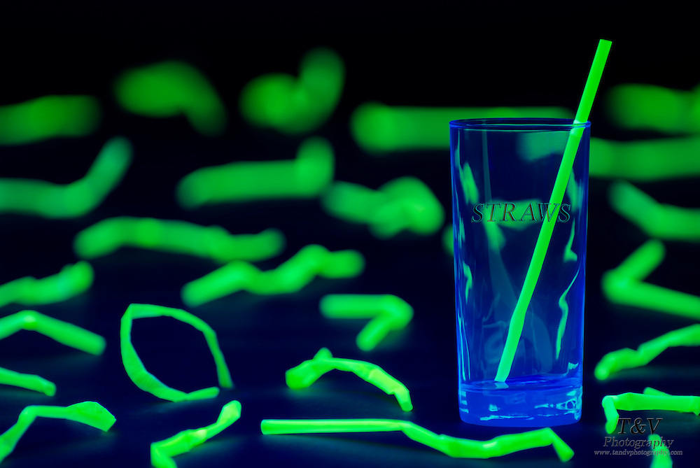 A straight, glowing straw remains intact inside a glass amongst a field of damaged straws.Blacklight