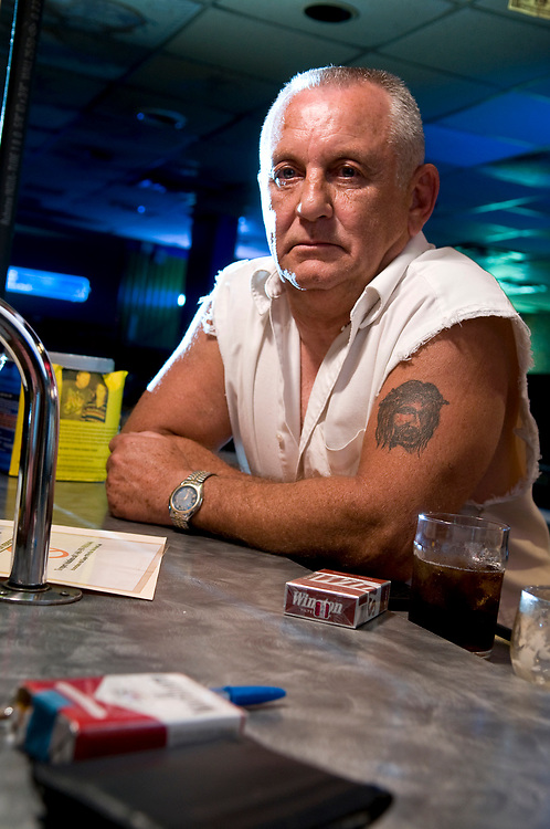 """Reverend Joe"" Sinnett, owner of Joez Lounge off of U.S. Route 30, leans against the bar Thursday, June 25. Sinnett has smoked for over 40 years and currently his establishment has received 22 complaints under Ohio's smoking ban."