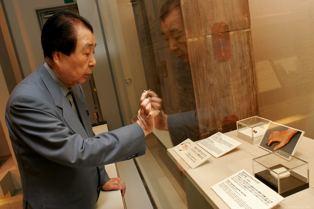 AKIHIRO TAKAHASHI.  Hiroshima A-Bomb survivor.  Former director of Hiroshima Peace Memorial Museum. Photo: inside the museum, in front of the picture and the remains of his nail that started growing abnormaly after the bombing.