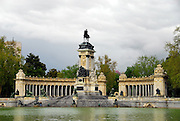 """A rainy spring day in the park. Everything looks clean and refreshed between showers in the Park Retiro, Madrid, Spain. The  """"Estanque del Retiro"""" is a large man made lake that is one of the centerpieces of the Park. This lake is a wonderful place to rent a row boat and glide past the semi circular colonnade monument to King Alfonso XII. The monument was built in 1922 by King Alfonso XII's mother. A large equestrian statue of the King anchors the monument."""