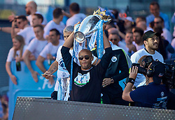 MANCHESTER, ENGLAND - Monday, May 20, 2019: Manchester City's captain Vincent Kompany holds up the Premier League trophy on an open-top bus as they parade through the city after winning a domestic treble of FA Premier League, Football League Cup and FA Cup trophies. (Pic by David Rawcliffe/Propaganda)