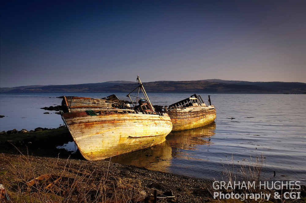 Three Rotting Wooden Fishing Boats on shoreline at Salen on Isle of Mull, Scotland.