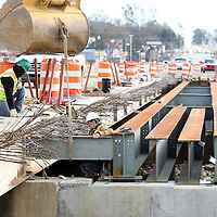 Adam Robison | BUY AT PHOTOS.DJOURNAL.COM<br /> Workers set beams for one of two new bridges, this one between Town Creek and Mud Creek, on East Main Street Monday morning in Tupelo.