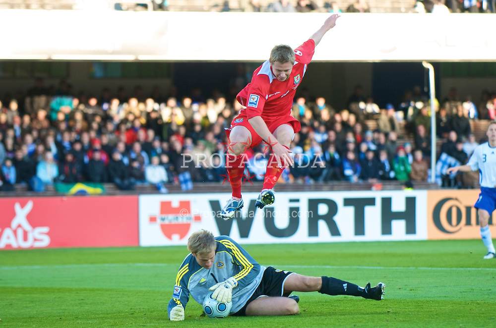 HELSINKI, FINLAND - Saturday, October 10, 2009: Wales' Simon Church and Finland's goalkeeper Jussi Jaaskelainen during the 2010 FIFA World Cup Qualifying Group 4 match at the Olympic Stadium. (Pic by David Rawcliffe/Propaganda)