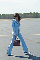 Woman in a suit walking at an airport outdoors
