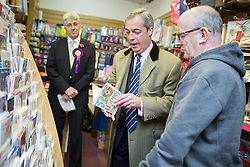 "© Licensed to London News Pictures . 03/11/2015 . Oldham , UK . UKIP leader NIGEL FARAGE (c) buying an 80th birthday card for his father from "" Greetings "" card and gift shop , from shop manager DAVID LOWICK (r) , in Royton Shopping Centre , at the launch of the party's campaign for the seat of Oldham West and Royton . The by-election has been triggered by the death of MP Michael Meacher . Photo credit : Joel Goodman/LNP"